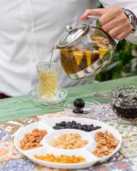 Adicionando chá de frutas no copo com nozes ao redor.