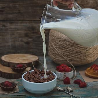 Adicionando leite da jarra de vidro aos cereais de chocolate. imahe