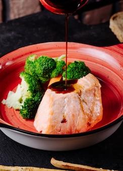 Adicionando molho teriyaki ao bife de salmão com brócolis na tigela rosa.