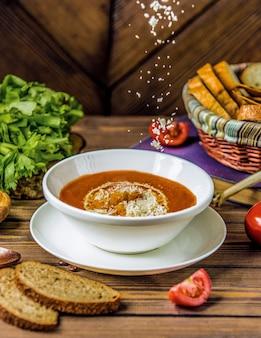 Adicionando parmesão picado e picado a uma sopa de tomate