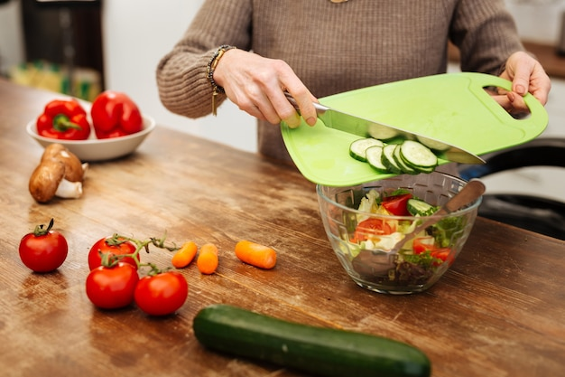 Adicionando pepinos picados. mulher atenciosa com um suéter bege jogando legumes na tigela de vidro enquanto jantava leve
