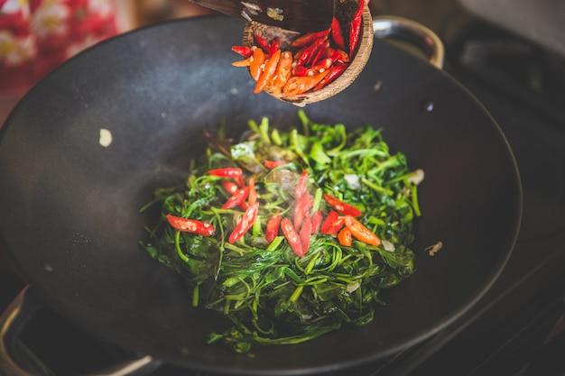 Adicionando pimenta vermelha em espinafre aquático salteados, close-up