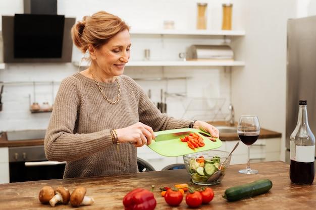 Adicionando tomates picados. mulher radiante de cabelos claros ficando na cozinha e preparando uma refeição leve enquanto toma vinho nas proximidades
