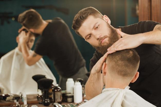Adicionando um pouco de cera ao visual. tiro horizontal de um barbeiro dando um penteado para seu cliente usando cera de cabelo