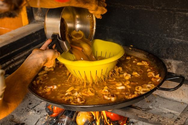 Adicionar caldo de peixe à paella valenciana com brasas e vegetais