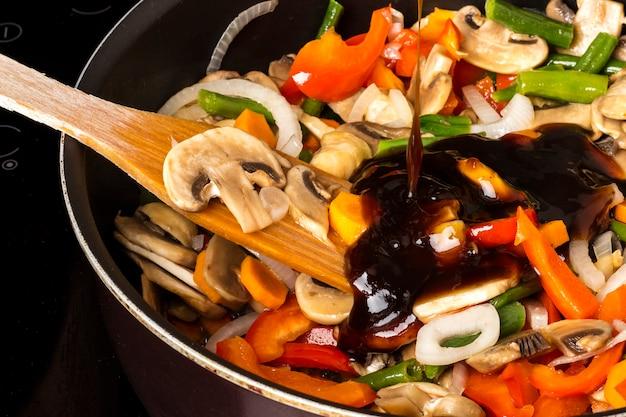 Adicionar molho a vegetais fritos com cogumelos em uma frigideira em um fundo escuro