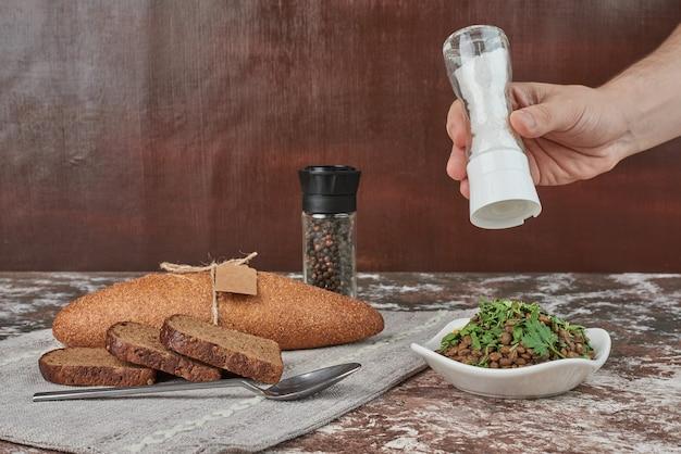 Adicionar sal na salada de lentilha.