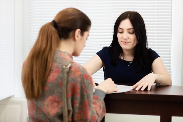 Administrador de jovem em uma clínica dentária no local de trabalho. admissão do cliente