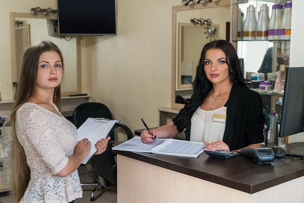 Administrador e cliente conversando perto da mesa da recepção