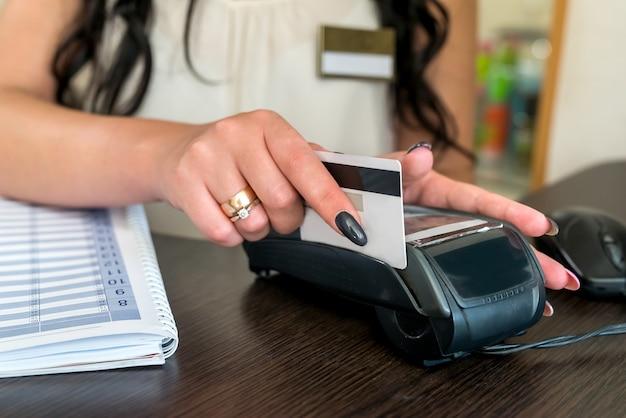 Administrador fazendo pagamento com cartão de crédito e terminal
