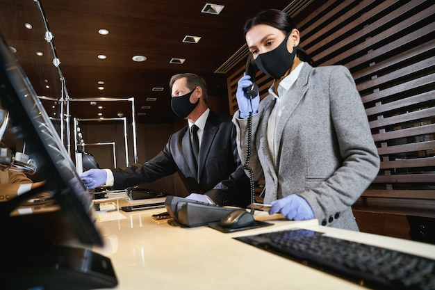 Administradora atendendo ligações enquanto um recepcionista ajudava os visitantes. máscaras médicas e luvas de borracha nelas