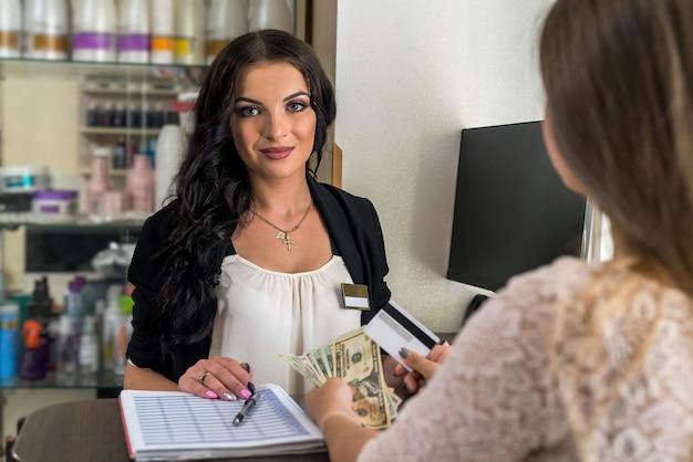 Administradora e cliente em salão de beleza com dólares e cartão de crédito