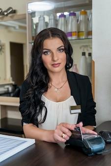 Administradora em salão de beleza fazendo pagamento com terminal