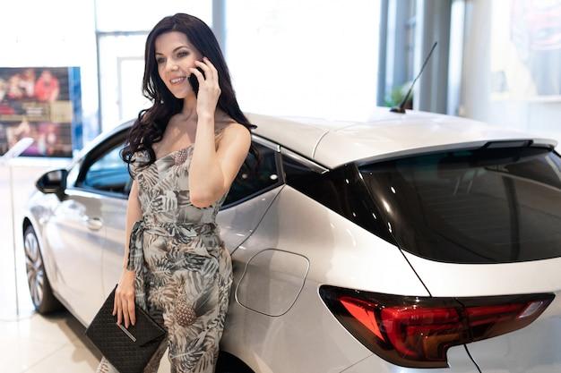 Admirável morena falando telefone e possuindo perto de seu carro novo no showroom da concessionária