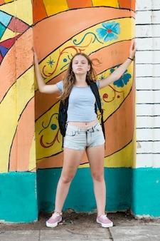 Adolescente à moda atrativa que levanta na frente da parede dos grafittis