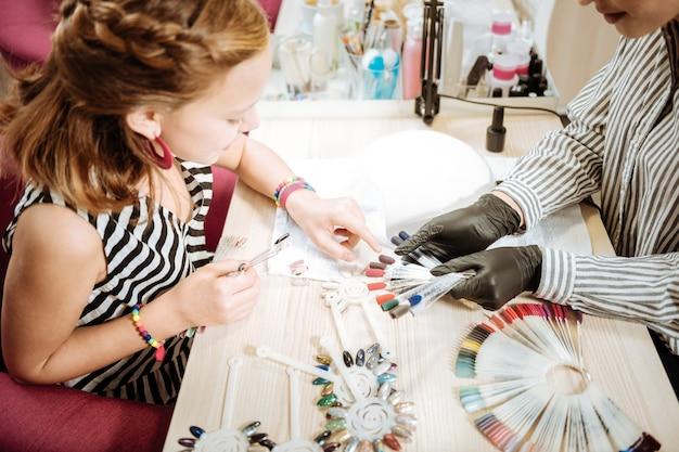 Adolescente. adolescente com vestido listrado e pulseiras mostrando a cor de goma-laca que ela deseja