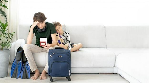 Adolescente adolescente triste com uma mala e nadadeiras fica em casa durante a pandemia de coronavírus.