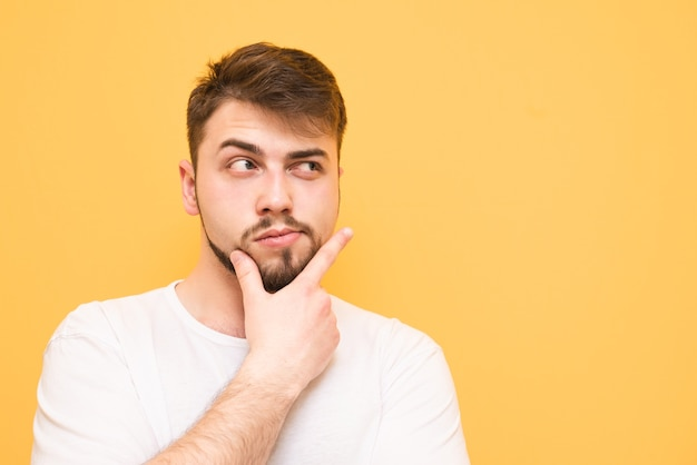 Adolescente adulto pensativo isolado no amarelo