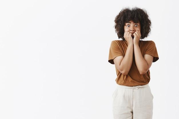 Adolescente afro-americana assustada em estupor olhos esbugalhados e cobrindo a boca para não gritar com as mãos sendo apavorada e assustada tremendo de medo e choque