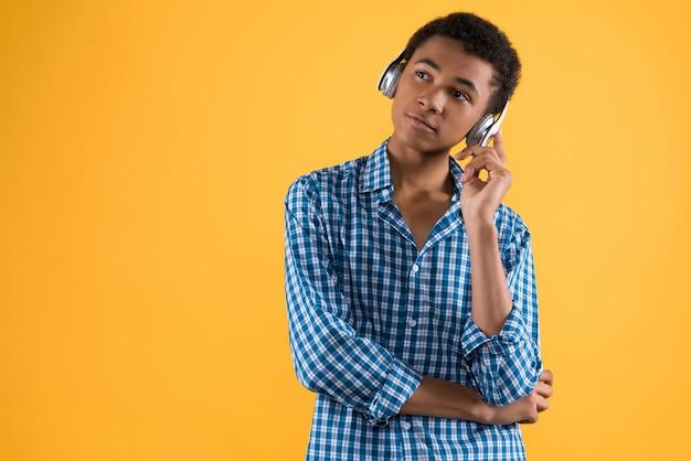 Adolescente afro-americano em fones de ouvido ouve música.
