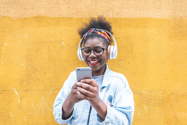 Adolescente afro-americano que usa o telefone celular fora.