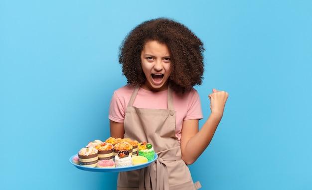 Adolescente afro bonito gritando agressivamente com uma expressão de raiva ou com os punhos cerrados celebrando o sucesso
