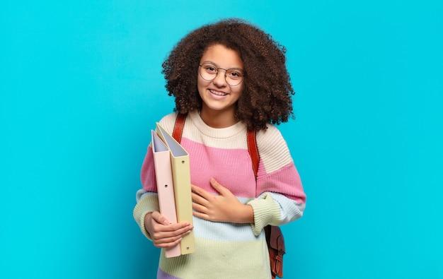 Adolescente afro bonito rindo alto de uma piada hilária, sentindo-se feliz e alegre, se divertindo