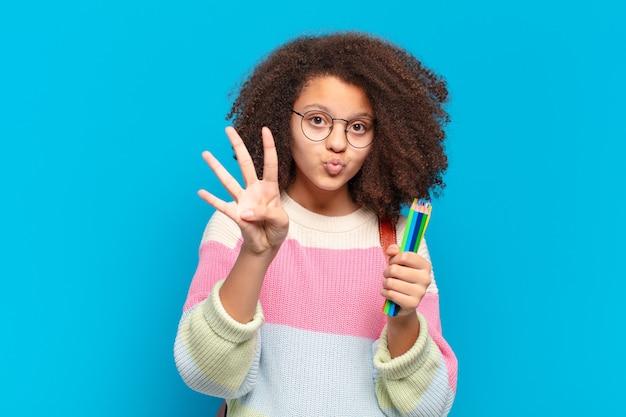 Adolescente afro bonito sorrindo e parecendo amigável, mostrando o número quatro ou o quarto com a mão para a frente