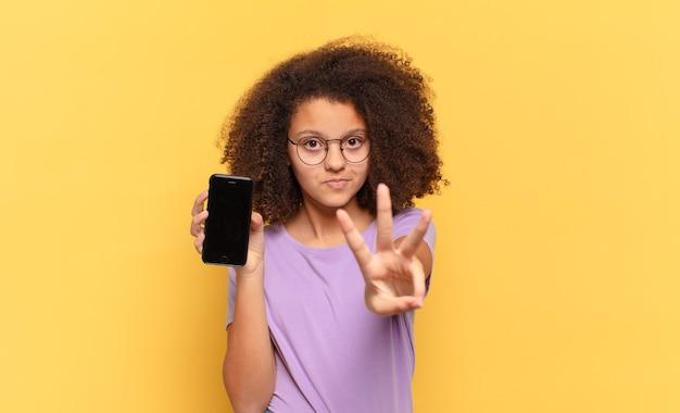 Adolescente afro bonito sorrindo e parecendo amigável, mostrando o número três ou terceiro com a mão para a frente, contando e segurando um celular