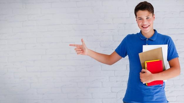 Adolescente alegre apontando para a esquerda