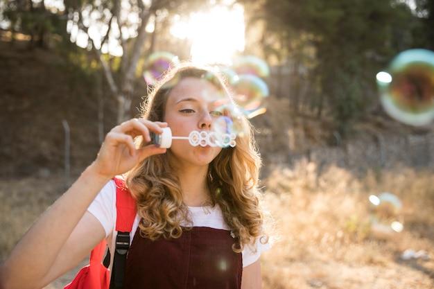 Adolescente alegre brincando com bolhas na natureza