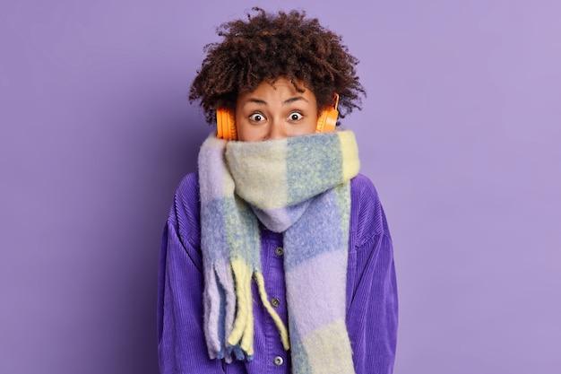 Adolescente alegre com cabelo encaracolado enrolado em um lenço que passa o tempo livre caminhando ao ar livre durante o dia de inverno ouve uma melodia agradável.