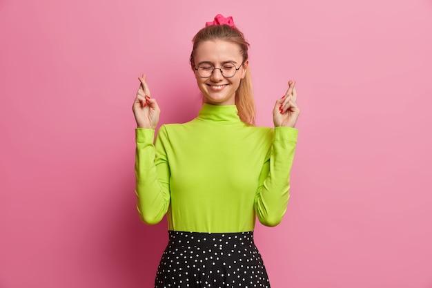 Adolescente alegre com sorriso gentil sonha com boa sorte e cumprindo algo que ela queria sorri positivamente com rabo de cavalo