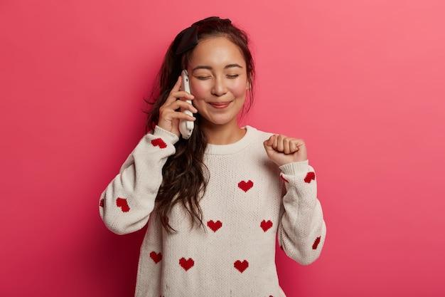 Adolescente alegre conversa ao telefone pelo celular, alegra-se com as boas notícias, ergue o punho cerrado, desfruta de uma comunicação feliz, fecha os olhos