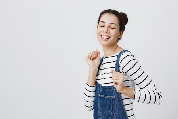 Adolescente alegre dançando com os olhos fechados e sorrindo