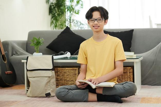 Adolescente alegre de óculos, sentado no chão em casa, lendo um livro ou romance de estudantes