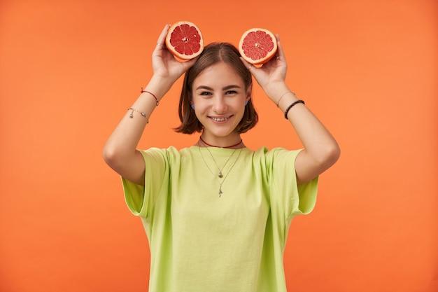 Adolescente, alegre e feliz com cabelo curto e castanho segurando uma toranja na cabeça, vestindo uma camiseta verde, aparelho dentário e pulseiras