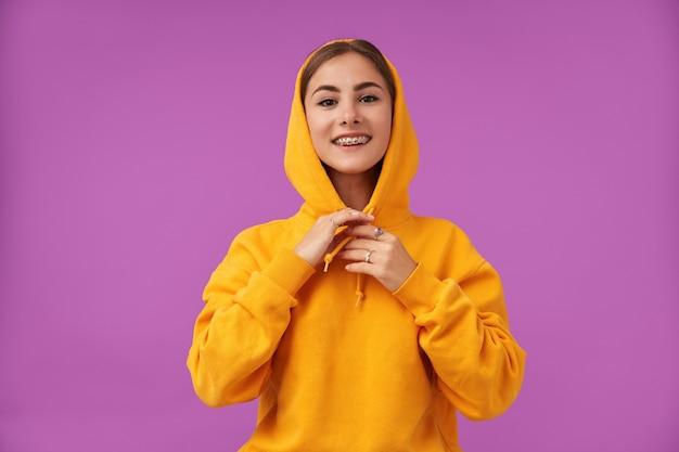 Adolescente, alegre e feliz, com cabelo curto morena tocando o capuz com as mãos, sobre a parede roxa. vestindo moletom laranja, anéis e aparelho dentário