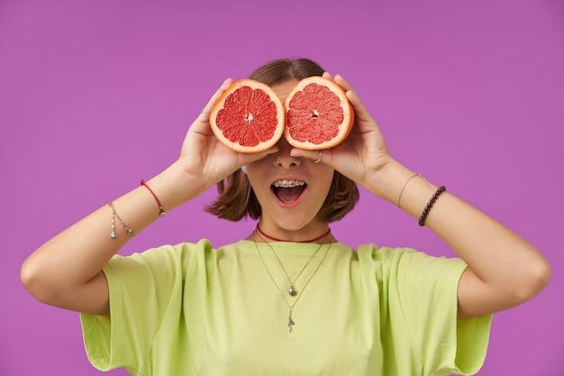 Adolescente, alegre e feliz, mulher com cabelo curto morena segurando grapefruit sobre os olhos. em pé sobre a parede roxa. vestindo camiseta verde, aparelho dentário, pulseiras e colar