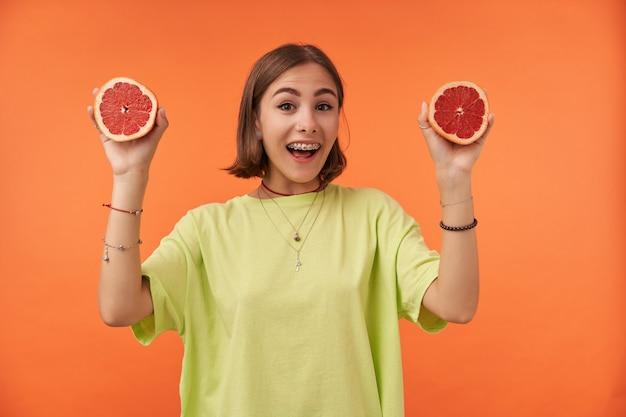 Adolescente, alegre e feliz, mulher com cabelo curto morena. segurando toranjas. fresco. em pé sobre a parede laranja. vestindo camiseta verde, suspensórios e pulseiras
