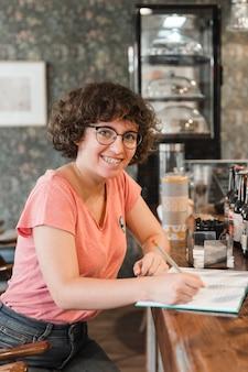 Adolescente alegre fazendo lição de casa no café