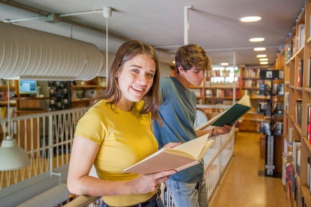Adolescente alegre lendo perto de namorado