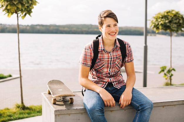 Adolescente alegre localizado na barreira perto da água