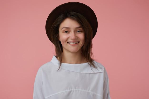 Adolescente, alegre, mulher olhando satisfeita com longos cabelos castanhos. vestindo blusa branca e chapéu preto. conceito emocional. isolado sobre parede rosa pastel