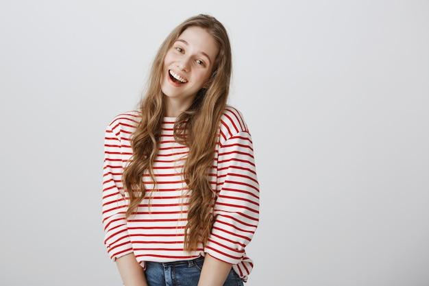 Adolescente alegre sorrindo adorável sobre uma parede cinza