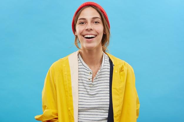 Adolescente alegre vestindo roupas da moda coloridas, regozijando-se com notícias positivas, olhando com um sorriso encantador, mostrando seus dentes brancos perfeitos. pessoas, estilo de vida, juventude e felicidade