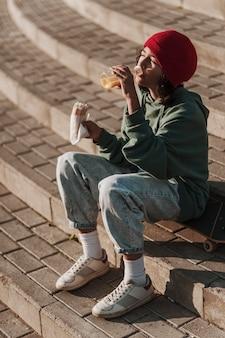 Adolescente almoçando no parque nas escadas