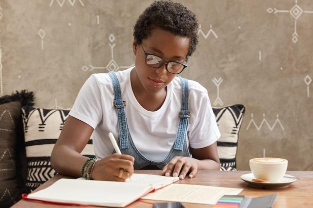 Adolescente ambicioso com pele morena e boycut, faz anotações necessárias na agenda