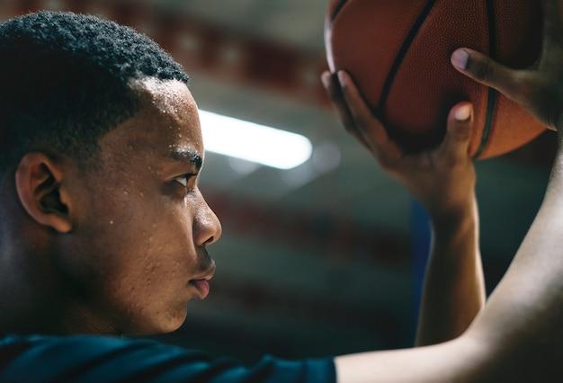 Adolescente americano africano concentrado em jogar basquete