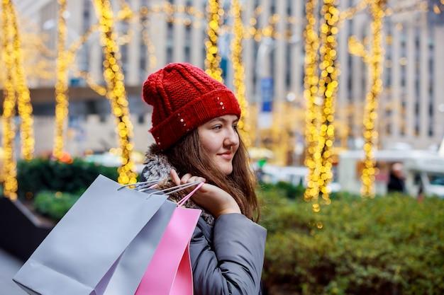 Adolescente andando com sacolas coloridas na rua de uma cidade, luzes coloridas bokeh